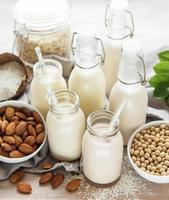 tipi alternativi di latte vegano in bottiglie di vetro foto