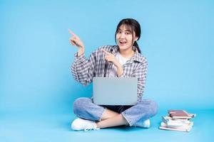 studentessa asiatica con espressione giocosa su sfondo blu foto