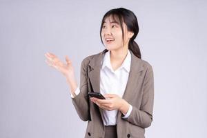 giovane imprenditrice asiatica che utilizza il telefono su sfondo bianco foto