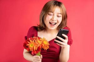 giovane ragazza che tiene fiori e usa il telefono con un'espressione allegra sullo sfondo foto