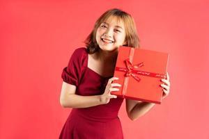 ragazza asiatica in abito con scatola regalo rossa con espressione allegra sullo sfondo foto