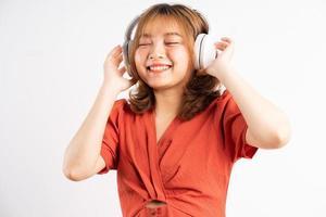 giovane ragazza asiatica che usa il suo telefono e indossa le cuffie per godersi la musica foto
