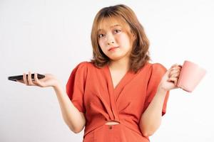 donna che tiene tazza d'acqua e telefono con espressione sullo sfondo foto