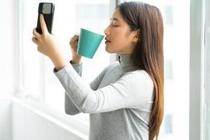 donna d'affari asiatica in piedi che prende la foto del selfie dalla finestra