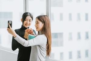 due donne d'affari asiatiche stavano chiacchierando vicino alla finestra durante la ricreazione foto