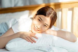 la bella donna asiatica si è appena svegliata al sorgere del sole foto