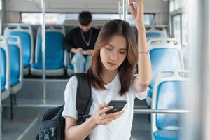 donna asiatica che utilizza smartphone sull'autobus? foto