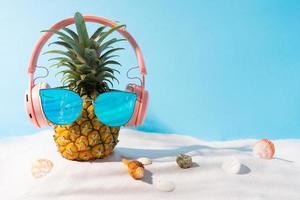 ananas che indossa cuffie e occhiali da sole sulla sabbia foto