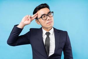 uomo d'affari asiatico che pensa al lavoro su sfondo blu foto