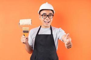 pittore asiatico che tiene il pennello in posa su sfondo arancione foto