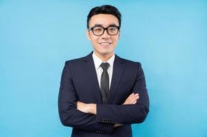 ritratto di uomo d'affari asiatico con le braccia incrociate e sorridente su sfondo blu foto