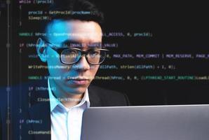 uomo asiatico che si concentra sulla programmazione con righe di codice in esecuzione sullo schermo foto