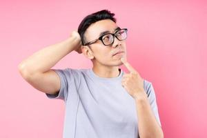 ritratto di uomo asiatico in posa su sfondo rosa con molte espressioni foto