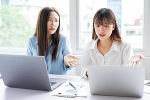 la donna d'affari asiatica e i suoi colleghi stanno discutendo tra loro sul piano di lavoro foto