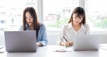 due giovani donne asiatiche sono concentrate sul lavoro foto