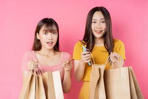 ritratto di due belle ragazze asiatiche che tengono molte borse della spesa su sfondo rosa foto
