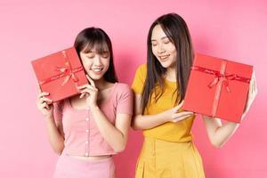 ritratto di due belle ragazze asiatiche che tengono una confezione regalo rossa su uno sfondo rosa foto