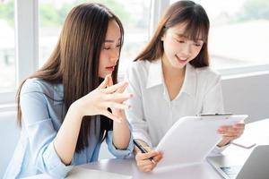 donna d'affari asiatica e colleghi che discutono di lavorare insieme foto