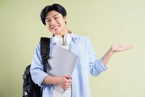 studente maschio asiatico che tiene la mano alla sua sinistra foto