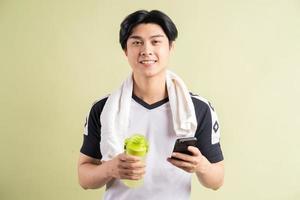 uomo asiatico che tiene acqua e smartphone in mano su sfondo verde foto