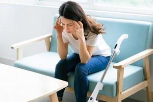 donna asiatica seduta su una sedia con un'espressione stanca mentre pulisce la casa foto