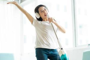 donna asiatica che ascolta musica e balla con un aspirapolvere foto