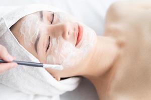 donna asiatica che fa trattamenti di bellezza, trattamenti termali e viene applicata la crema sul viso foto