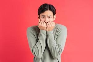 una foto di un bell'uomo asiatico che si copre il viso con le mani per la paura