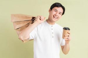 un bell'uomo d'affari asiatico che tiene in mano le borse della spesa e una tazza di caffè da portare via foto