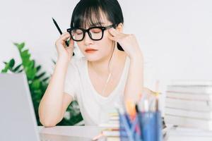 la donna d'affari asiatica è stanca e ha mal di testa con molto lavoro alla scadenza foto