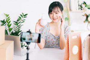 donna d'affari asiatica utilizza gli smartphone per trasmettere in streaming la vendita di cosmetici su siti di social network e siti di e-commerce. foto
