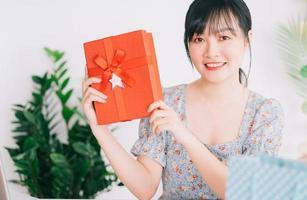 giovane donna asiatica in diretta streaming per fare regali al pubblico che guarda il suo streaming su piattaforme di social network foto