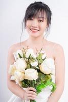 una foto ritratto di una sposa asiatica che indossa un abito da sposa e sorride magnificamente, con in mano un mazzo di fiori.