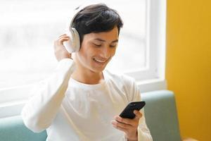 uomo asiatico seduto, godendo la musica foto