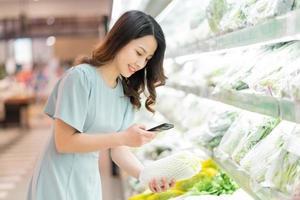 la ragazza sceglie di comprare la verdura al supermercato foto