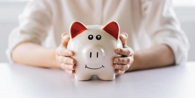 la mano della donna che tiene il salvadanaio sul tavolo, risparmia denaro e investimenti finanziari foto
