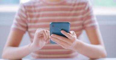 immagine di una giovane donna asiatica che usa lo smartphone foto