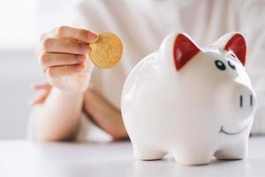 donna mano che tiene moneta da mettere nel salvadanaio sul tavolo, risparmiare denaro e investimenti finanziari foto
