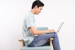 bell'uomo con laptop seduto sul divano di lavoro foto