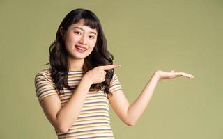 giovane bella donna asiatica in posa sullo sfondo foto