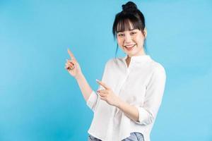bella donna asiatica in piedi che punta su sfondo blu foto