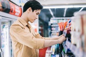 il giovane asiatico si chiedeva mentre faceva shopping al minimarket di notte foto