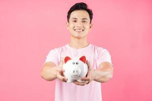 giovane uomo asiatico che tiene salvadanaio su sfondo rosa foto