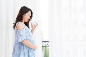 bella donna che si tiene la pancia e tiene una tazza di latte in piedi vicino alla finestra foto
