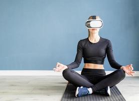 giovane donna bionda in abiti sportivi che indossano occhiali per realtà virtuale meditando sul tappetino fitness foto