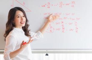 l'insegnante asiatica sta riscrivendo la lezione alla lavagna foto