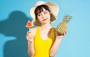bella donna asiatica che indossa una tuta gialla su sfondo blu e mangia frutta tropicale, concetto estivo foto