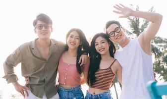 un gruppo di giovani asiatici si gode una gita al mare durante le vacanze estive foto
