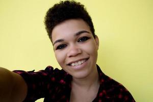 bella e felice donna afroamericana con i capelli corti su uno sfondo giallo, prende un selfie, ritratto ravvicinato foto