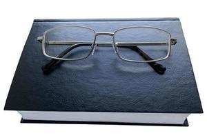 libro nero e occhiali su sfondo bianco, isolato foto